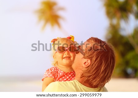 Happy father and cute little daughter at beach, family care - stock photo