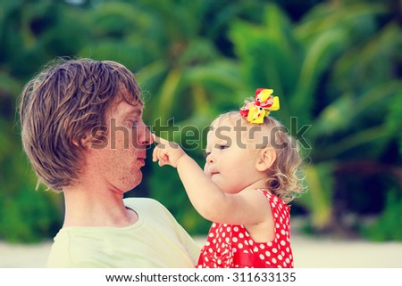 Happy father and cute little daughter play at tropical beach - stock photo