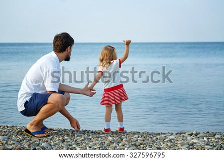 Happy father and daughter at the seaside look far away. The concept of a happy family holiday. - stock photo