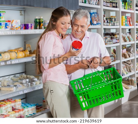 Happy father and daughter buying product in supermarket - stock photo
