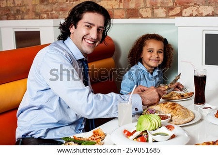 Happy father and daughter eating in a restaurant - stock photo