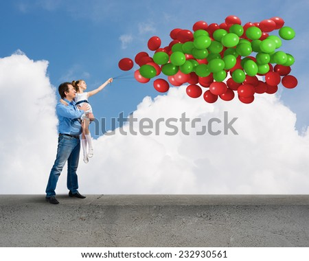 Happy father and daughter outdoor with bunch of balloons - stock photo