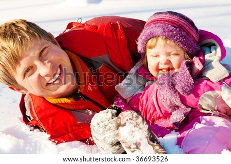 Happy father and daughter playing in snow - stock photo
