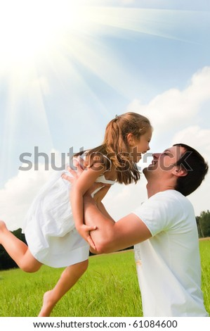 Happy father and daughter playing in the meadow - stock photo