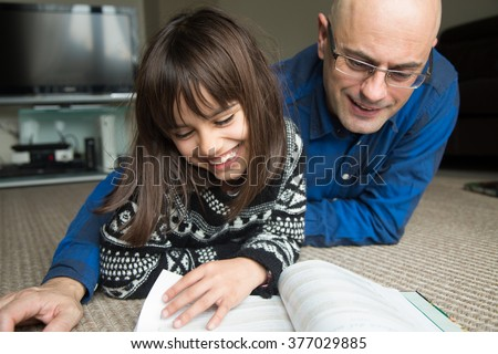 Happy father and daughter reading a book on the floor at home - stock photo