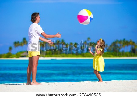 Happy father and daughter running on the beach with ball having fun together - stock photo