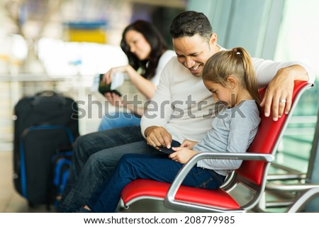 happy father and daughter using tablet computer at airport while waiting for their flight - stock photo