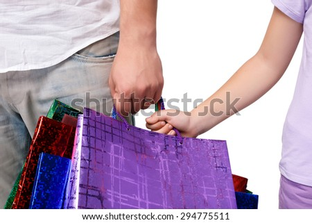 Happy father and daughter with shopping bags standing at studio, isolated on white background. close-up of hands holding shopping bags - stock photo