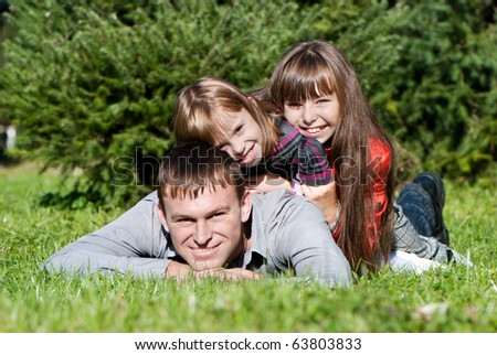 Happy father and daughters in park
