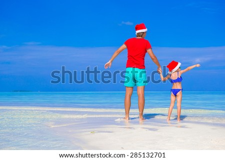 Happy father and his adorable daughter in Santa Hat at tropical beach  - stock photo