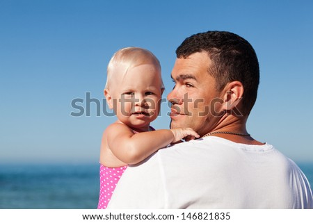 Happy father and his adorable little daughter at beach - stock photo