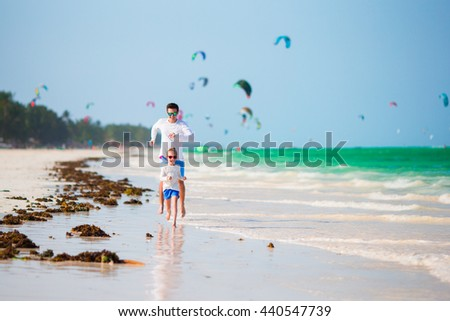 Happy father and his adorable little daughter at tropical beach. Caucasian family having fun together on suumer vacation on white beach running and enjoying their holidays - stock photo