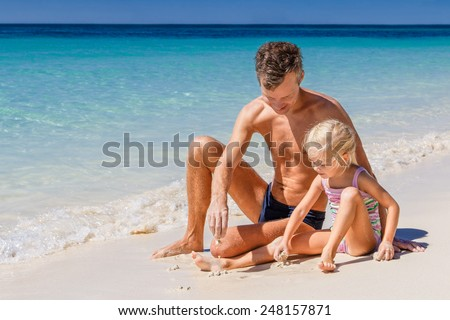 Happy father and his adorable little daughter at tropical beach, playing in the sand