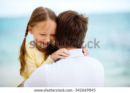 Happy father and his adorable little daughter outdoors at beach - stock photo