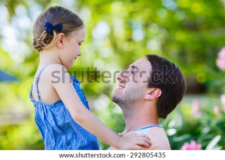 Happy father and his adorable little daughter outdoors smiling to each other - stock photo