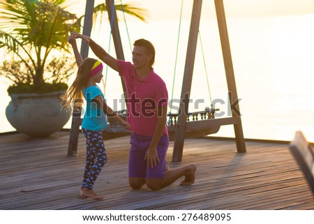 Happy father and his adorable little daughter relax at evening - stock photo