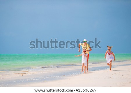 Happy father and his adorable little daughters at tropical beach  - stock photo
