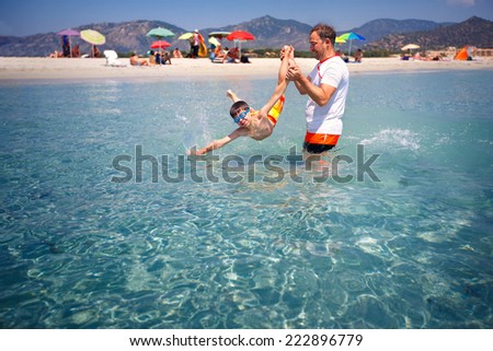 Happy father and his cute little son having fun on beach - stock photo
