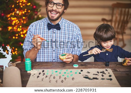 Happy father and his cute son practicing potato printing before Christmas - stock photo