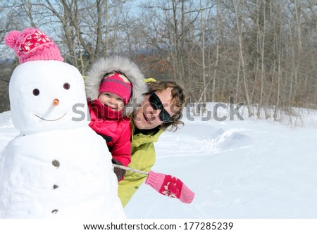 Happy father and his cute toddler daughter building the snowman - stock photo