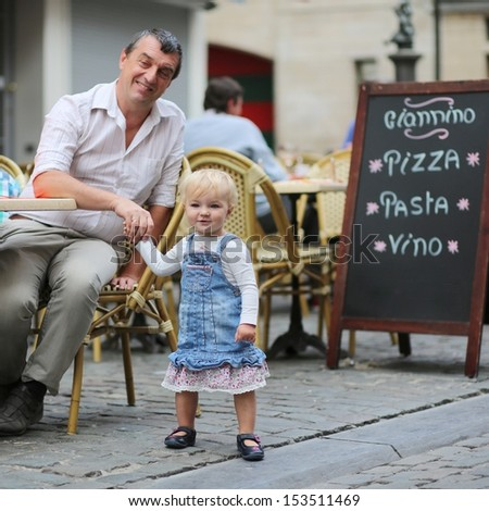 Happy father and his daughter, cute little baby girl, are having fun together in Italian cafe sitting at a table on outdoor terrace on a warm summer day - stock photo