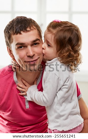 Happy father and his daughter together on window background - stock photo