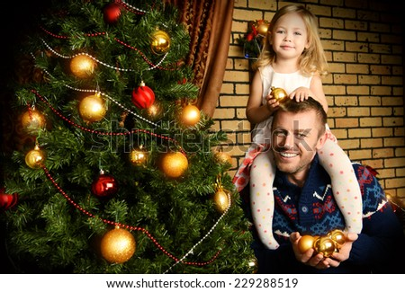 Happy father and his little daughter decorating the Christmas tree at home. - stock photo