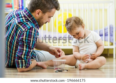 happy father and his little daughter playing with various buttons at home