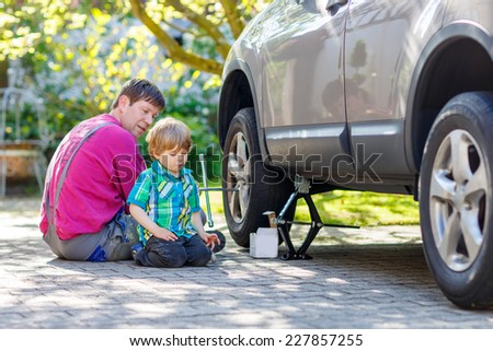Happy father and his little toddler boy repairing car and changing wheel together on warm sunny day, outdoors. Dad teaching his son. - stock photo