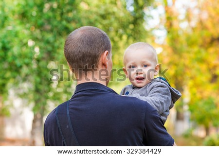 Happy father and his son outdoors. Child hugging daddy and looking out behind his back