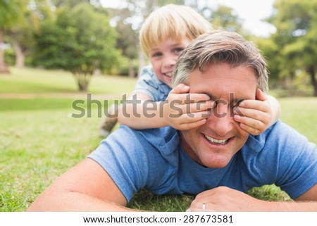 Happy father and his son smiling at camera on a sunny day - stock photo