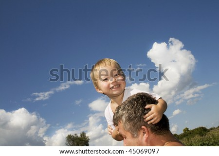 Happy father and his son straddle on shoulders