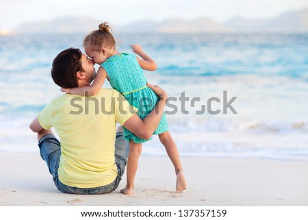 Happy father and his sweet little daughter at beach - stock photo