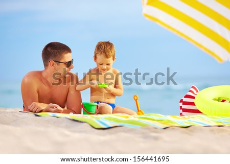 happy father and kid playing toys on the beach - stock photo