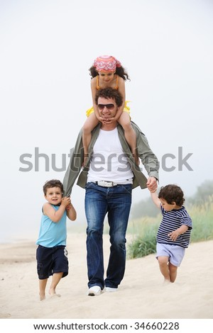 Happy father and kids on the beach - stock photo