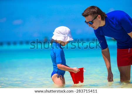 Happy father and little daughter have fun on tropical beach - stock photo
