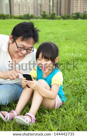 happy father and little girl watching the smart phone