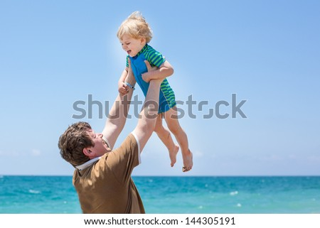 Happy father and little son having fun at beach vacation