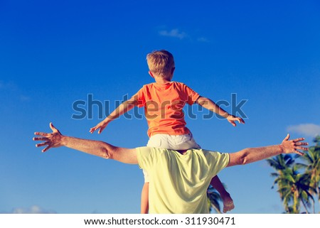 happy father and little son on shoulders play on sky at tropical beach - stock photo