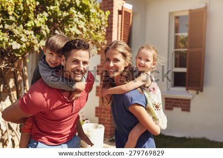 Happy father and mother looking at camera while piggybacking their son and daughter. Happy young family of four playing in their backyard on a sunny day. - stock photo