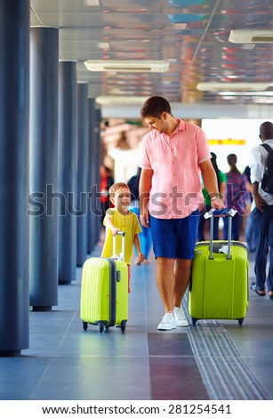 happy father and son are going for boarding on airplane, summer vacation - stock photo