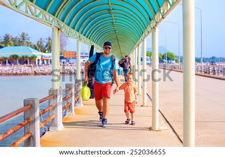 happy father and son are going to board a ship at the pier station - stock photo
