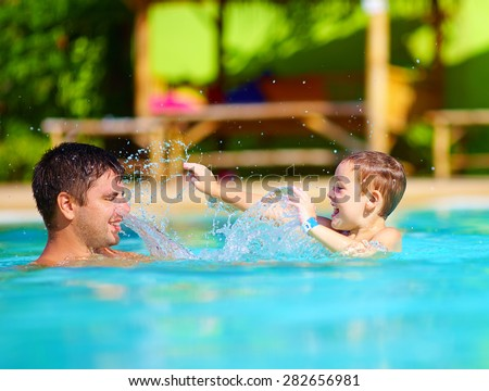 happy father and son dabbling in pool water, summer holiday - stock photo