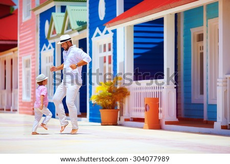 happy father and son enjoy life, dancing on caribbean street - stock photo