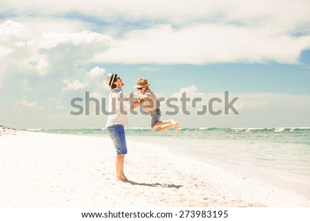 Happy father and son enjoying beach time on summer vacation in a sunny day - stock photo