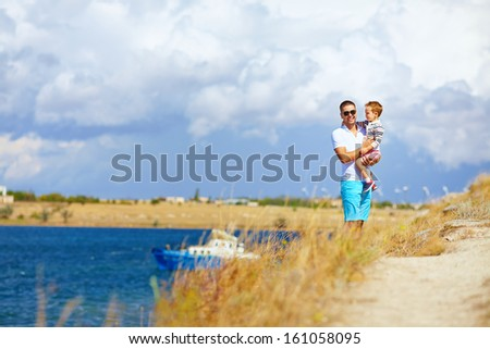 happy father and son enjoying seaside landscape - stock photo