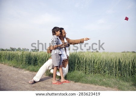Happy father and son flying a kite in field - stock photo