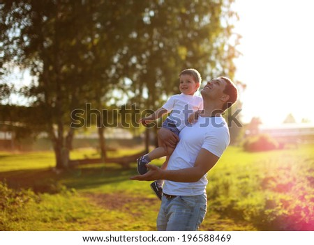 Happy father and son having fun, enjoying sunny summer day. Sunlight on the sunset - stock photo