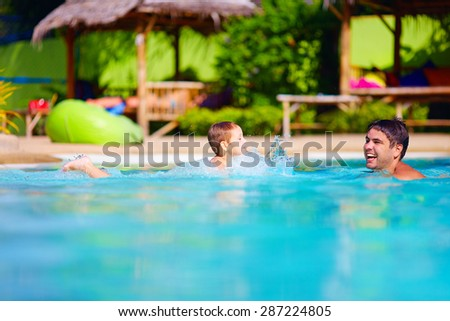 happy father and son having fun in pool water, summer holiday - stock photo
