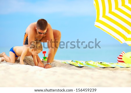 happy father and son having fun in sand on the beach